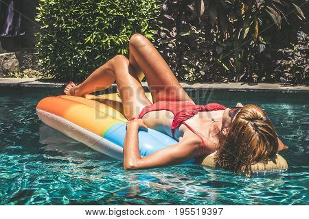 Young pretty woman with perfect tanned body lying on air mattress in the pool in summer and having fun. Relaxing sexy lady in sunglasses. Tropical Bali island.