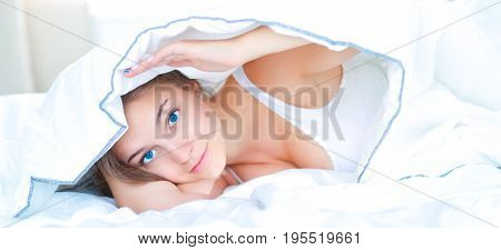 Young beautiful woman lying in bed under cover.