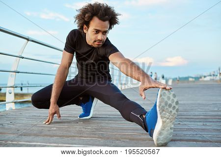 Healthy athlete dark-skinned boy stretching on wooden platform in the morning. Sporty male with bushy hairstyle warming up his legs before running exercise outdoors. Fit man doing yoga at seaside. Fitness and motivation.