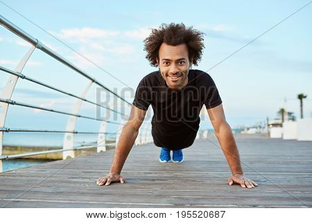 Young Afro-American man runner with athletic body doing exercises during workout outdoors. Healthy lifestyle concept. Cheerful dark-skinned guy doing plank position.