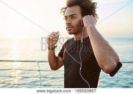 Portrait of Afro-American athlete wearing white earphones, getting ready for jogging. Running at the sunrise behind the sea. Healthy lifestyle concept.