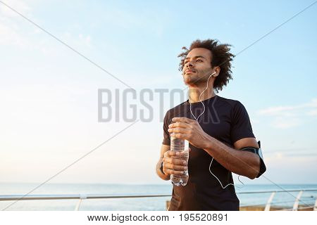 Man athlete drinking water out of plastic bottle after hard running workout. Dark-skinned male sportsman looking at the sky while running, enjoying view.
