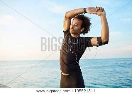 Man runner with bushy hairstyle stretching before active workout. Male athlete wearing earphones in black sport clothing doing exercises against blue sea background