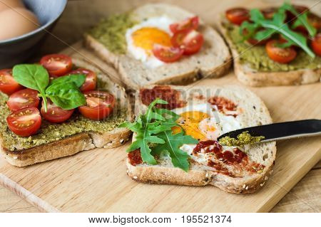 Healthy toasts with egg arugula cherry tomatoes spinach pesto sauce tomato sauce and multi cereal bread. Breakfast sandwiches