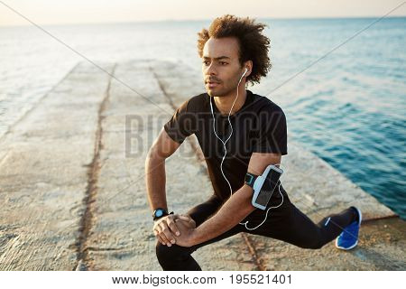 Man athlete in black sportswear stretching legs with lunge hamstring stretch exercise on pier. Listening music in earphones. Fitness and motivation.