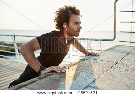 Confident sportsman with bushy hairstyle doing exercises on pier early in the morning. Placing his arms on platform while listening music. Warming up before running.
