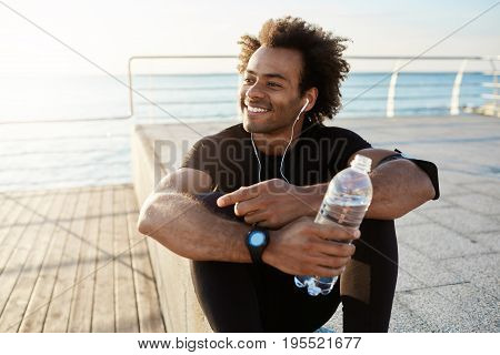 Cheerful dark-skinned muscular athlete in black sport clothing sitting on pier after sport activities wearing white earphones. Smiling runner enjoying morning workout and drinking water. Motivation concept.