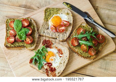 Breakfast toasts on wooden cutting board. Healthy sandwiches with cherry tomato egg spinach arugula pesto sauce tomato sauce and bread with sesame seeds. Balanced breakfast