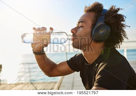 Fit dark-skinned man athlete drinking water out of plastic bottle after hard cardio running workout. Muscular man wearing stylish black sport clothing with big headphones on listening music for better training.