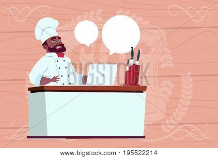 African American Chef Cook Working At Laptop Computer Cartoon Restaurant Chief In White Uniform Sit At Desk Over Wooden Textured Background Flat Vector Illustration