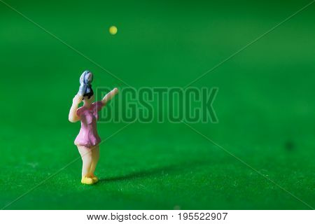 Tennis player figurines serving tennis ball on grass court