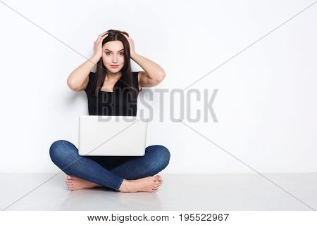 Schocking news. Worried woman sitting at home on floor and looking on screen of laptop while holding hands on her head.