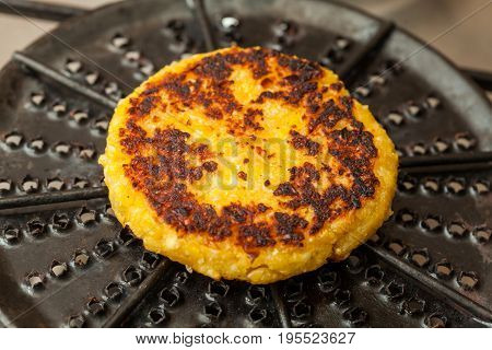 Traditional Colombian Arepa de Choclo Preparation : Corn bread being roasted on a round grill
