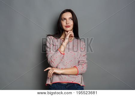 Pensive young woman looking upwards. Beautiful relaxed girl dreaming about something, lost in thoughts, gray studio background