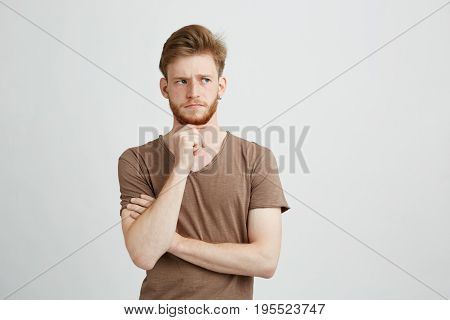 Portrait of serious young man thinking considering looking in side over white background. Copy space.