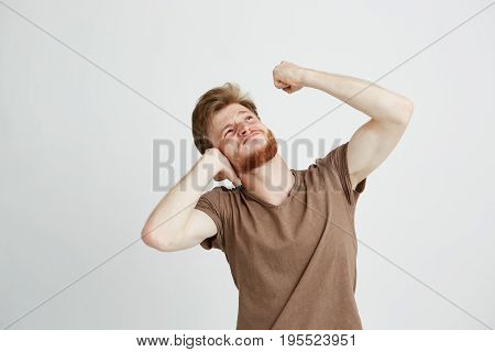 Portrait of young angry man with beard closing ears looking up showing fist over white background. Copy space.