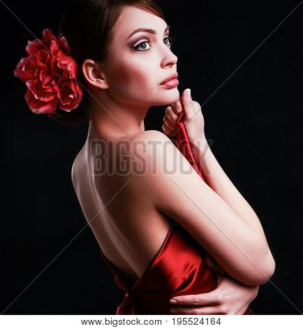 Young woman on red dress, isolated on black background.