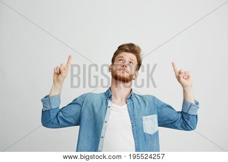 Portrait of cheerful young handsome man smiling pointing finger up over white background. Copy space.