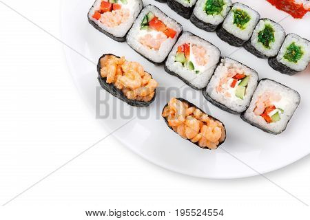 Traditional japanese food delivery. Sushi set served on white plate closeup. Colorful rolls and gunkan assortment at white background with copy space, top view