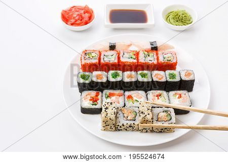 Japanese food restaurant. Sushi set served on white platter with soy sauce, ginger and wasabi and chopsticks picking one piece. Pov at white background with copy space