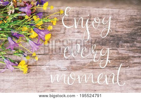 Enjoy Every Moment motivational quote.Wildflowers bouquet on vintage wooden background.