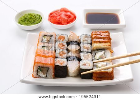 Japanese food restaurant. Sushi set served on white platter with soy sauce, ginger and wasabi and chopsticks picking one piece. Pov at white background