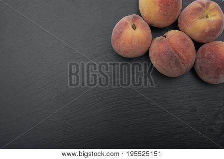 Ripe Peach ion black background of slate or stone.