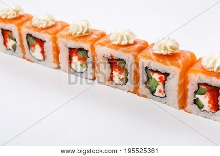 Sushi japanese restaurant delivery. Set of salmon and avocado rolls with decoration of philadelphia cheese isolated at white, pov. Healthy food background with copy space