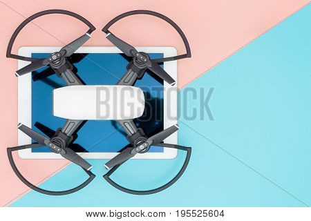 Tablet for controlling drone on blue and pink copy space flat lay. Flying quadcopter gadgets on tablet.