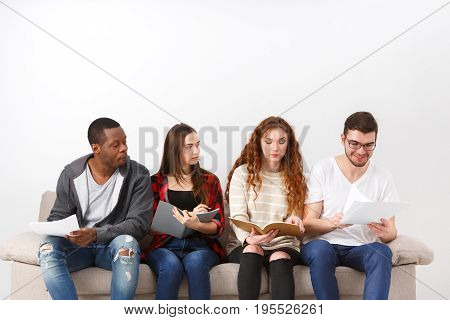 Multiethnic young students study, preparing for exam, sitting on sofa in living room, studio shot