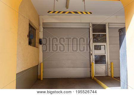 Garage lift gates in yellow house, gates of parking for cars in residential building