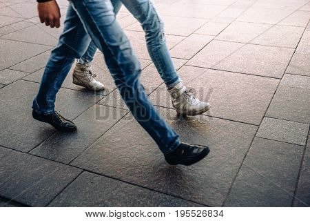 Legs in jeans of young man and woman in street shoes walking or going fast. Fast rhythm of life of modern city concept
