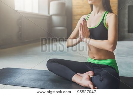 Attractive girl practicing yoga sitting in padmasana. Young woman in half lotus pose, namaste on mat at sport club interior, crop, copy space