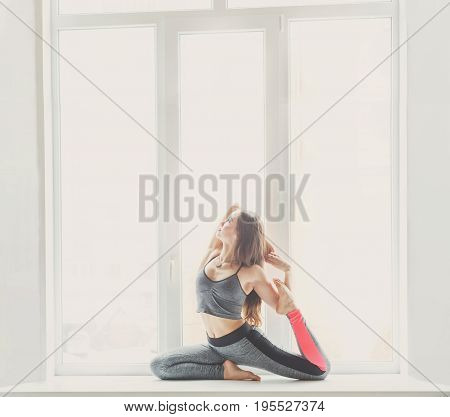 Young woman makes yoga pose at window backlight, copy space. Girl do mermaid posture. Healthy lifestyle