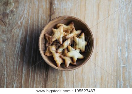 Top view image of small biscuits in many shapes in wooden cup on wood table background