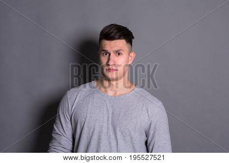 Negative human emotion. Man expressing annoyance on face, grimacing on grey studio background