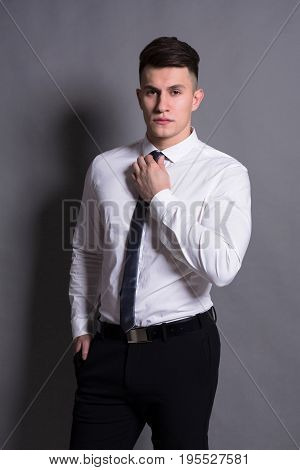 Successful businessman. Confident young man standing at gray studio background