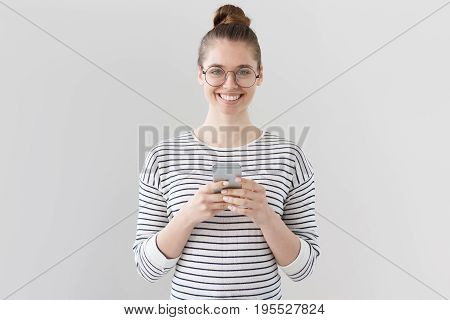 Indoor Shot Of Good-looking Young Female With Hair Tied In Bun Isolated On Gray Background Looking S