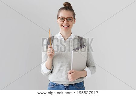 Studio Shot Of Positive Student Girl Isolated On Grey Background Wearing Glasses, Sweater And Jeans,