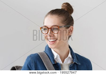 Indoor Closeup Of Nice Teenager Girl Wearing Big Trendy Spectacles And Denim Jacket Isolated On Gray