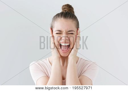 Closeup Portrait Of Young European Female Isolated On Gray Background Having Opened Mouth While Cryi