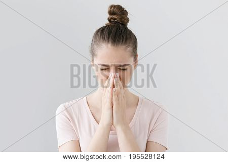 Closeup Of Young European Female Isolated On Gray Background Looking Stressed, Putting Hands Togethe