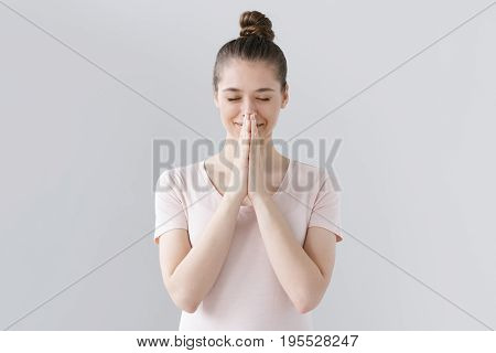Picture Of Young Girl Dressed Casually Without Make Up Isolated On Grey Background, Having Put Hands