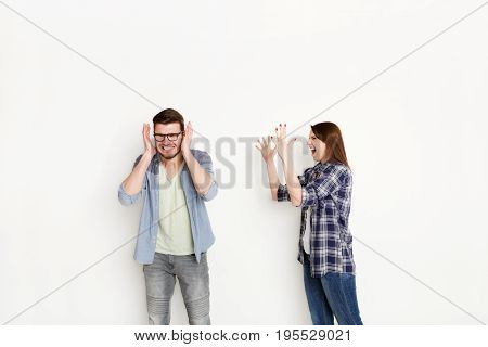 Couple arguing. Angry woman shouting to boyfriend while he covering ears with hands, studio shot