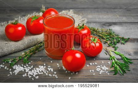 Freshly squeezed Tomato juice in glass. Ingredients for Tomato juice are crystalline salt, cherry tomatoes, rosemary greens and thyme on burlap. Rustic vintage gray wood background.