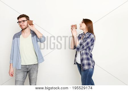Communication and fun. Young casual couple talking through tin can phone, isolated on white background