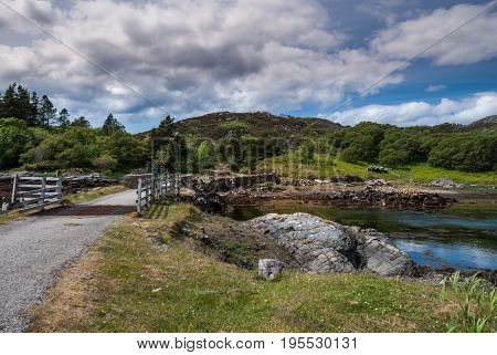 Assynt Peninsula Scotland - June 7 2012: Short stone bridge with cattle grill over creek landing into Atlantic Ocean inlet South of Loch An Arbhair under heavy sky. Forested hills and ocean waters.