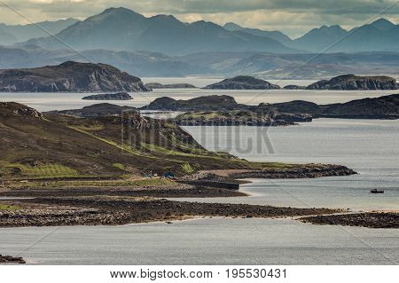 Assynt Peninsula Scotland - June 7 2012: Looking out from Altandhu hamlet over Atlantic Ocean inlet with multitude of rocky islets under heavy storm sky. Mountain peaks in background. Moored sloop.