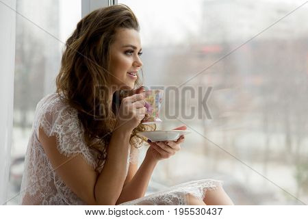 Sexy Young Woman In Erotic Transparent Underwear Drinks Coffee On Window Sill. Cityscape On Backgrou