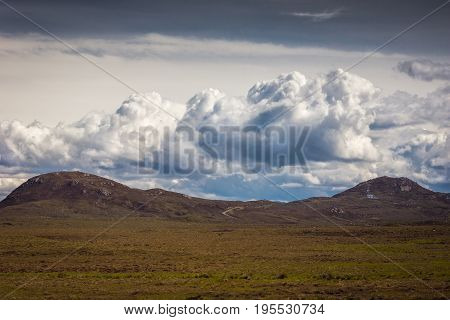 Assynt Peninsula Scotland - June 7 2012: Hilly scenery under gray sky with white towering clouds dry desert-like vegetation on plateau in front at Brae of Achnahaird. Total desolation.